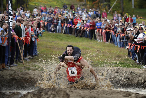 <div class='meta'><div class='origin-logo' data-origin='AP'></div><span class='caption-text' data-credit='AP Photo/Robert F. Bukaty'>Elliot Storey races through the mud pit while carrying his wife, Giana Storey, both of Westbrook, Maine, to win the North American Wife Carrying Championship, Oct. 8, 2016.</span></div>