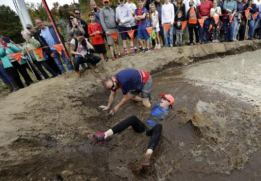 <div class='meta'><div class='origin-logo' data-origin='AP'></div><span class='caption-text' data-credit='AP Photo/Robert F. Bukaty'>Robin Gahan gets dumped into the mud pit after her husband, Steven Gahan, of Rochester, N.Y., lost his balance during the North American Wife Carrying Championship.</span></div>