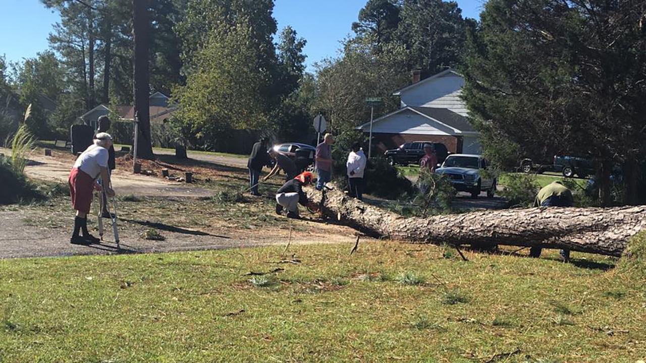 Neighbors help clear storm damage in the Cliffdale West subdivision in Fayetteville