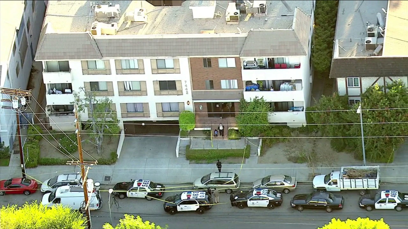 Los Angeles Police Department vehicles are seen outside an apartment complex in Van Nuys on Monday, Oct. 10, 2016, after a woman was pushed out of a window and died.