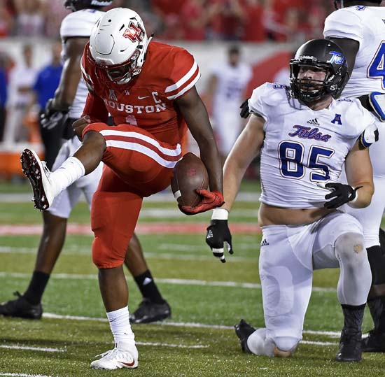 <div class='meta'><div class='origin-logo' data-origin='AP'></div><span class='caption-text' data-credit='Eric Christian Smith'>Houston quarterback Greg Ward Jr., left, celebrates a first down as Tulsa defensive end Kolton Shindelar (85) watches in the first half.</span></div>