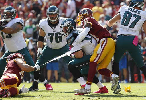 "<div class=""meta image-caption""><div class=""origin-logo origin-image ap""><span>AP</span></div><span class=""caption-text"">Philadelphia Eagles quarterback Carson Wentz's jersey tears as he is tackled by Washington Redskins outside linebacker Ryan Kerrigan, left, and free safety Will Blackmon. (AP Photo/Alex Brandon)</span></div>"