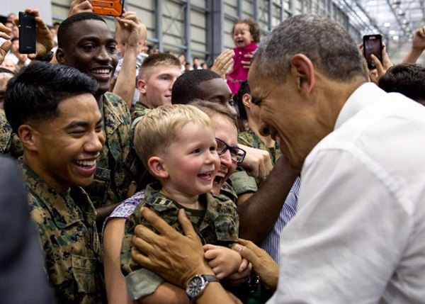 "<div class=""meta image-caption""><div class=""origin-logo origin-image none""><span>none</span></div><span class=""caption-text"">President Obama smiling as he meets a toddler while visiting the Marine Corps Air Station in Iwakuni, Japan. (Pete Souza, Chief Official White House Photographer)</span></div>"