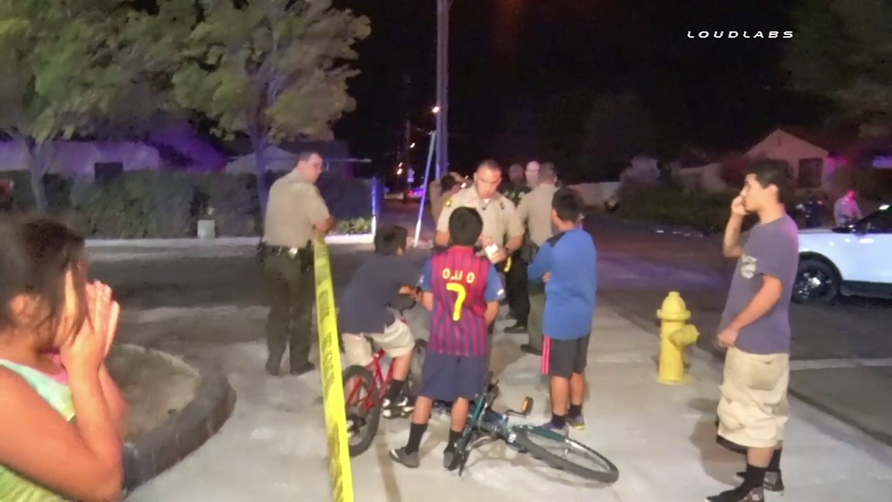 A San Bernardino County sheriff's deputy speaks with a group of boys at the scene of a hit-and-run crash in Victorville on Thursday, Oct. 20, 2016.