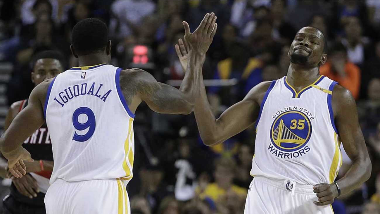 Warriors' Kevin Durant, right, is congratulated by Andre Iguodala after scoring during a preseason NBA basketball game Friday, Oct. 21, 2016, in Oakland, Calif.