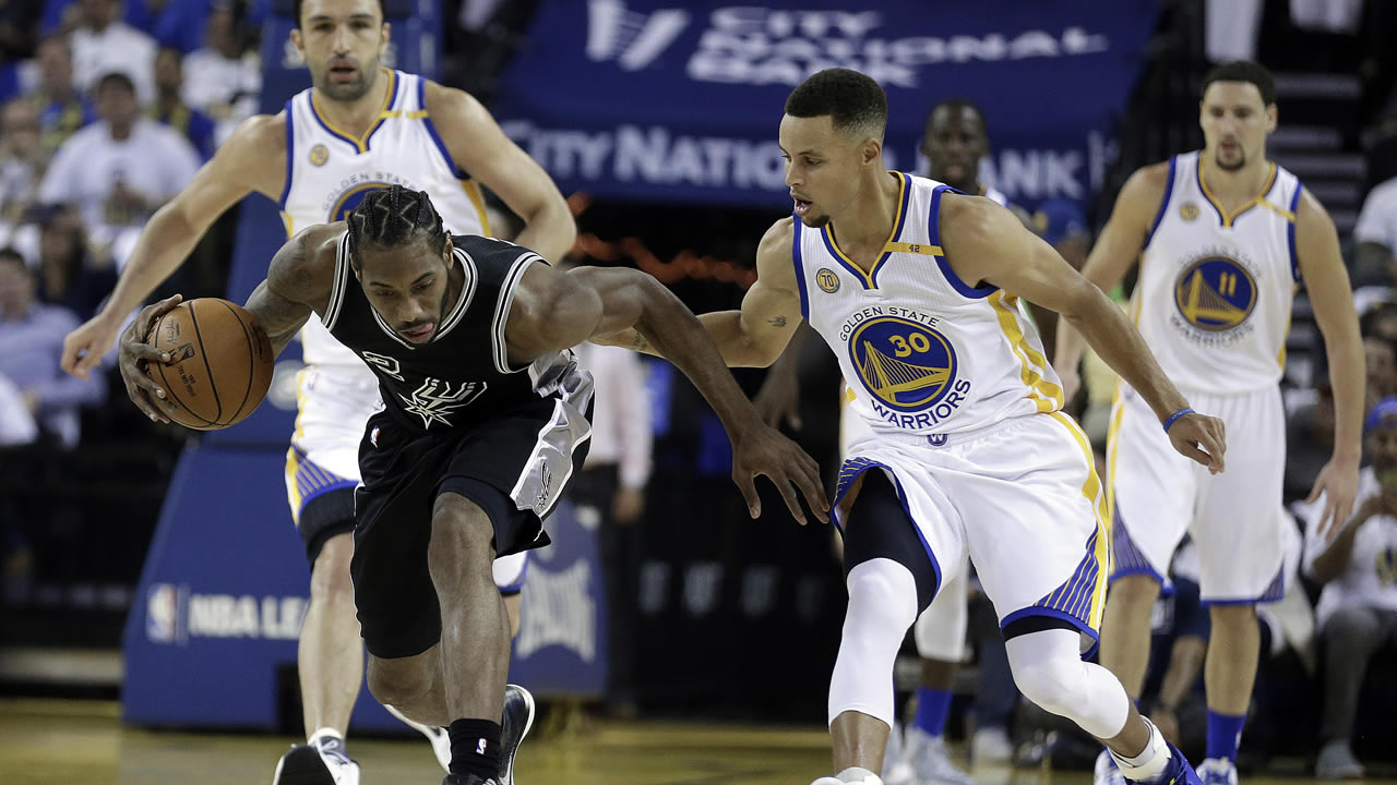 Spurs' Kawhi Leonard, left, recovers a loose ball past Warriors' Stephen Curry during a home opener on Tuesday, Oct. 25, 2016, in Oakland, Calif. (AP Photo/Ben Margot)