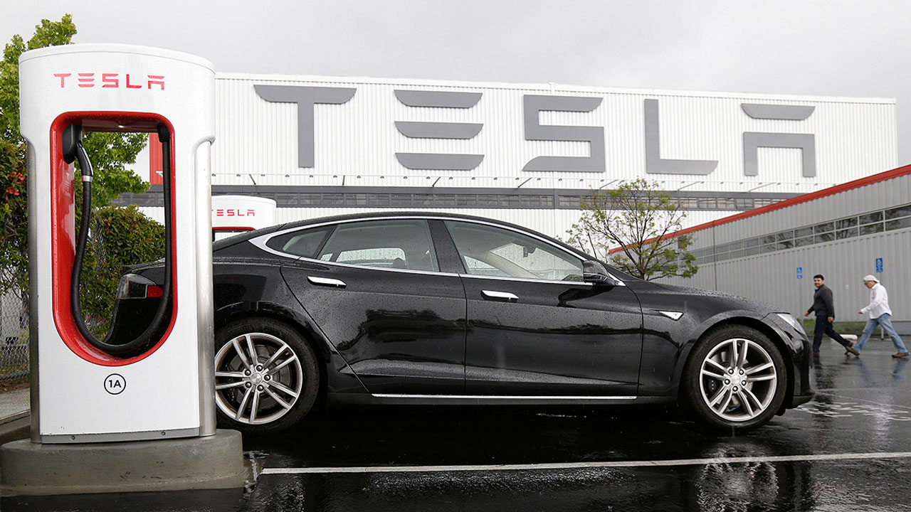 A Tesla vehicle is parked at a charging station outside of the Tesla factory in Fremont, Calif.