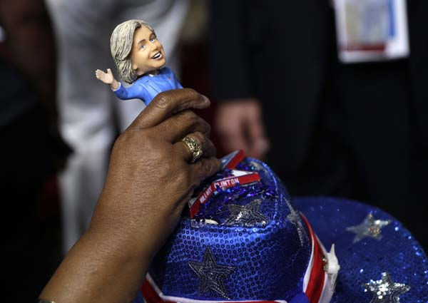 <div class='meta'><div class='origin-logo' data-origin='AP'></div><span class='caption-text' data-credit='AP Photo/John Locher'>A delegate adjust a Hillary Clinton bubble-head doll on her head</span></div>