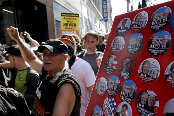 <div class='meta'><div class='origin-logo' data-origin='AP'></div><span class='caption-text' data-credit='AP Photo/Patrick Semansky'>Protesters march past buttons for Republican presidential candidate Donald Trump</span></div>