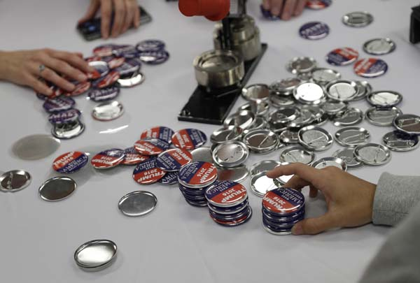 <div class='meta'><div class='origin-logo' data-origin='AP'></div><span class='caption-text' data-credit='AP Photo/John Locher'>People make campaign buttons while waiting for Republican presidential candidate Donald Trump</span></div>