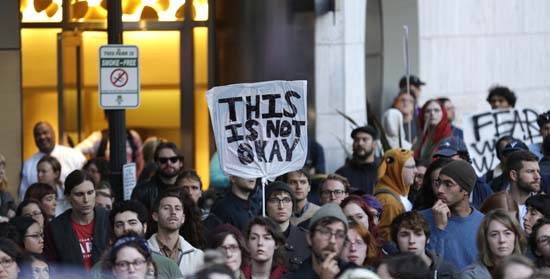 <div class='meta'><div class='origin-logo' data-origin='AP'></div><span class='caption-text' data-credit='Ted S. Warren'>A protester holds sign that reads &#34;This is Not OK&#34; during a protest against the election of President-elect Donald Trump, Wednesday, Nov. 9, 2016, in downtown Seattle.</span></div>