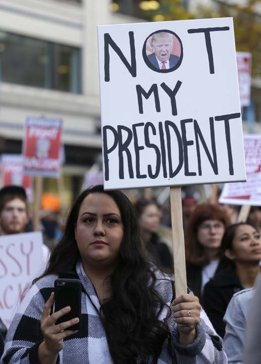 <div class='meta'><div class='origin-logo' data-origin='AP'></div><span class='caption-text' data-credit='Ted S. Warren'>A protester holds sign that reads &#34;Not My President&#34; during a protest against the election of President-elect Donald Trump, Wednesday, Nov. 9, 2016, in downtown Seattle.</span></div>