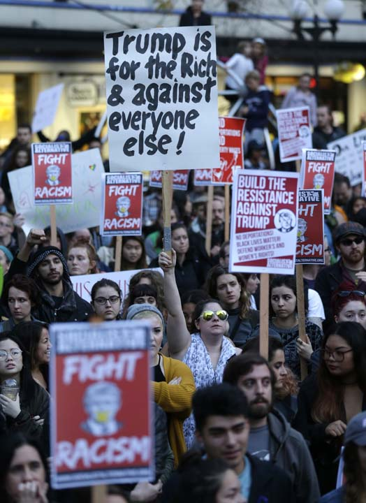 <div class='meta'><div class='origin-logo' data-origin='AP'></div><span class='caption-text' data-credit='AP'>Protesters hold signs during a protest against the election of President-elect Donald Trump, Wednesday, Nov. 9, 2016, in downtown Seattle. (AP Photo/Ted S. Warren)</span></div>