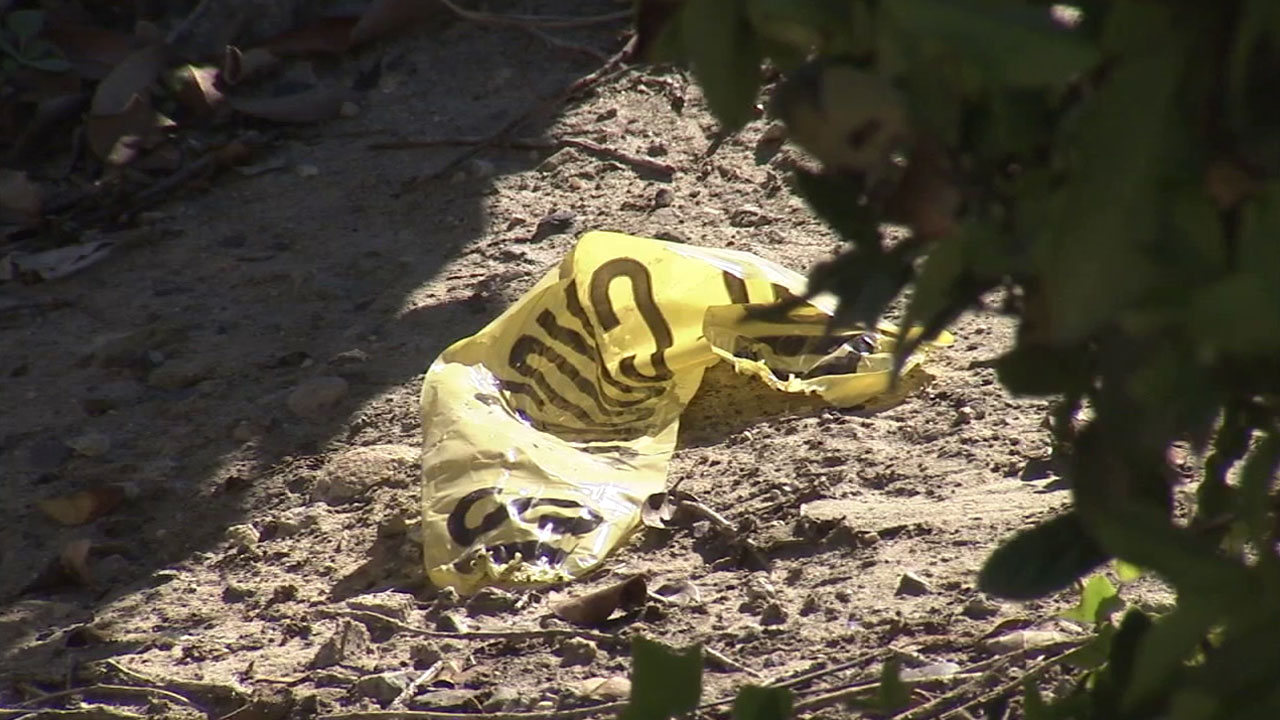 A piece of police crime tape sits in the area where a woman's body was found behind a bank in Mission Viejo.