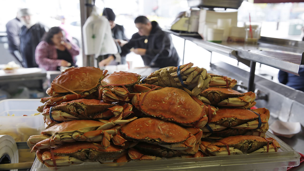 A stack of imported Dungeness crabs are shown for sale as people eat them in the background at Fisherman's Wharf Tuesday, Dec. 22, 2015, in San Francisco