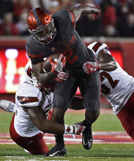 "<div class=""meta image-caption""><div class=""origin-logo origin-image ap""><span>AP</span></div><span class=""caption-text"">Houston running back Duke Catalon, center, is attacked by Louisville linebacker Henry Famurewa, left, and linebacker Vince Lococo during the first half. (AP Photo/Eric Christian Smith)</span></div>"