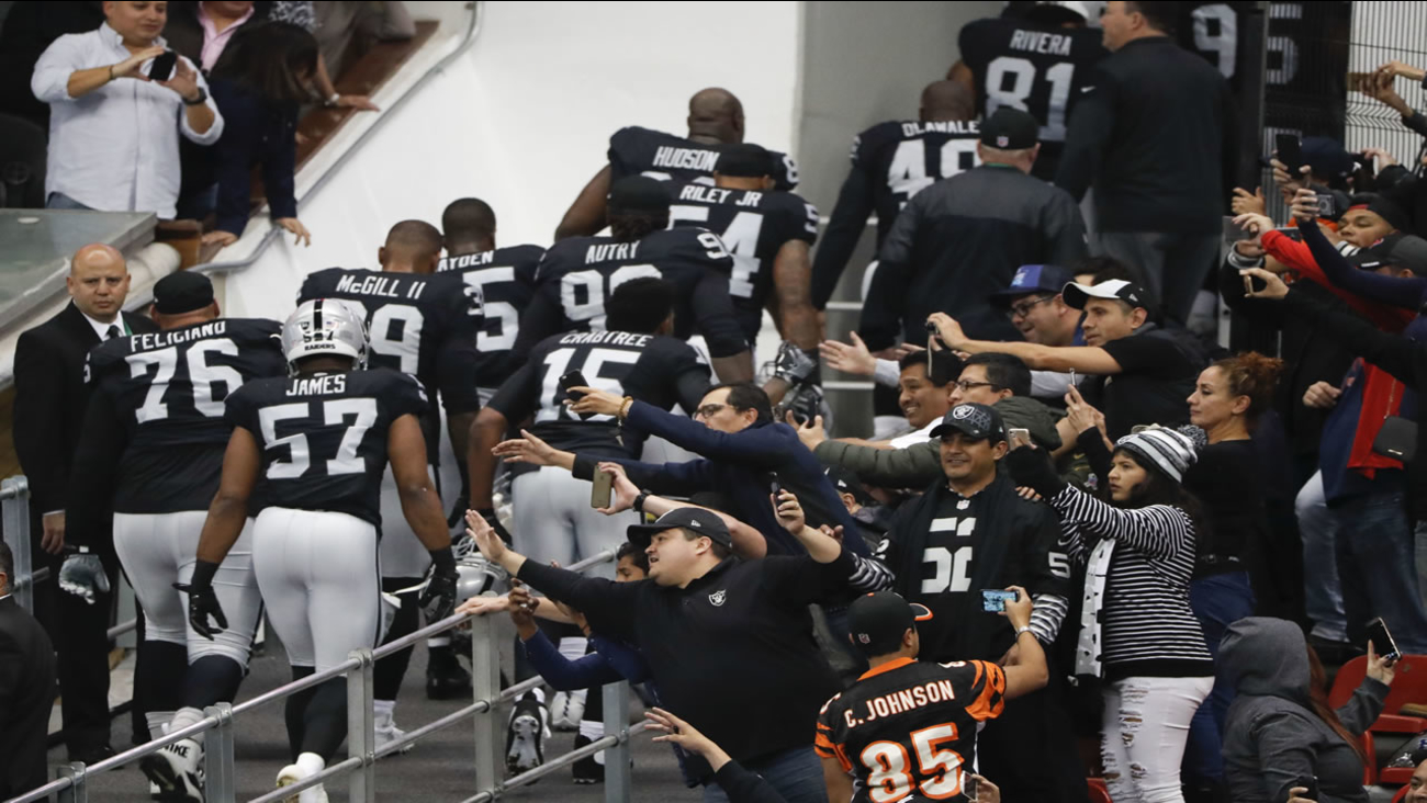 Fans reach out as the Oakland Raiders players make their way into a tunnel before an NFL football game against the Houston Texans Monday, Nov. 21, 2016, in Mexico City.