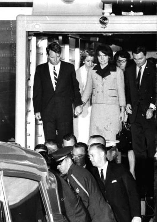 "<div class=""meta image-caption""><div class=""origin-logo origin-image none""><span>none</span></div><span class=""caption-text"">First Lady Jacqueline Kennedy, her dress stained with blood, stands with Attorney General Robert F. Kennedy, as they watch the casket of her husband placed in an ambulance (AP Photo/XCB)</span></div>"
