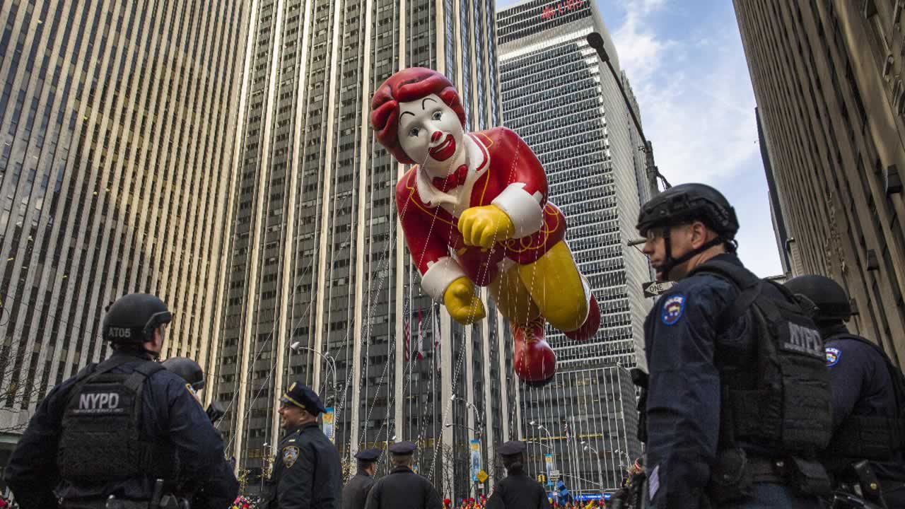 The Ronald McDonald balloon makes its way across Sixth Avenue as heavily armed police stand guard during the Macy's Thanksgiving Day Parade, Thursday, Nov. 26, 2015.