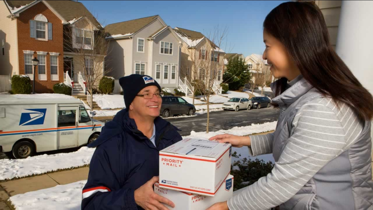 U.S. Postal Service letter carrier delivering packages during the holidays
