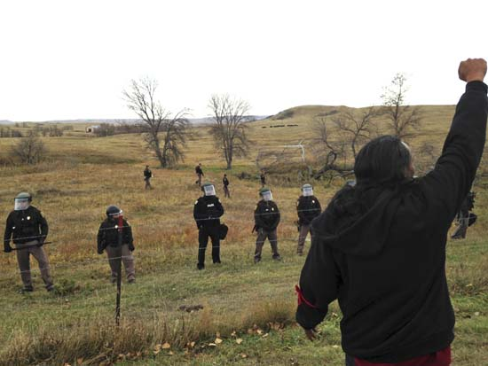 <div class='meta'><div class='origin-logo' data-origin='none'></div><span class='caption-text' data-credit='(AP Photo/James MacPherson)'>A Dakota Access pipeline protester defies law enforcement officers who are trying to force them from a camp on private land in the path of pipeline construction.</span></div>