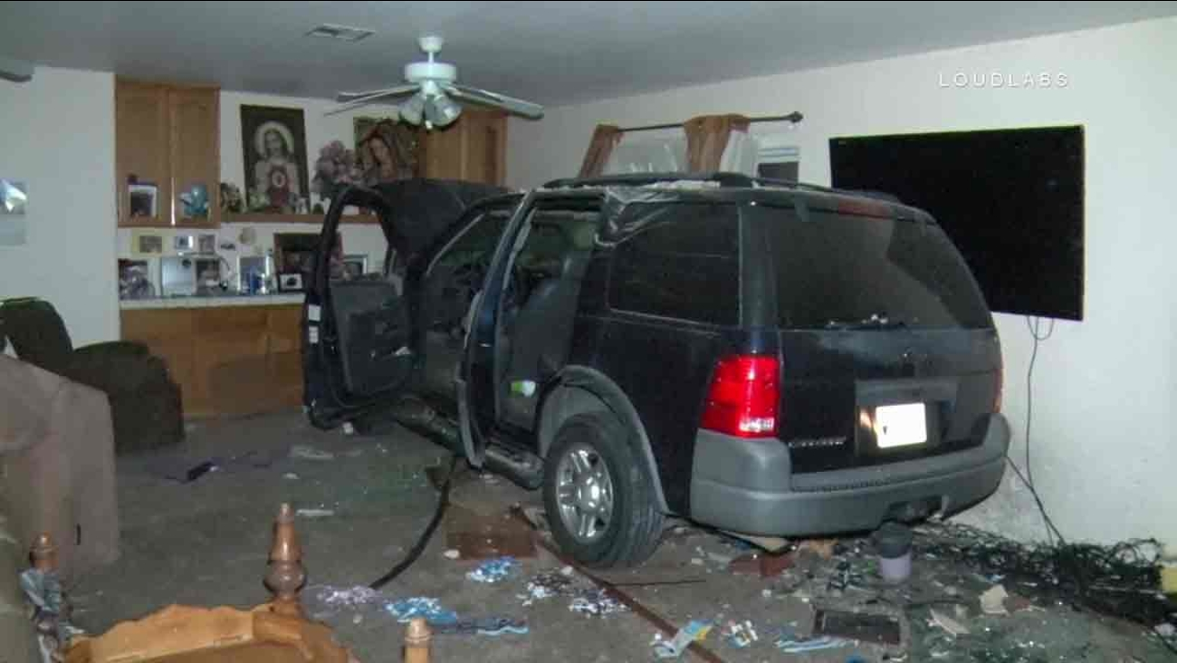 An SUV sits inside a living room at a Hesperia home following a crash on Nov. 27, 2016.