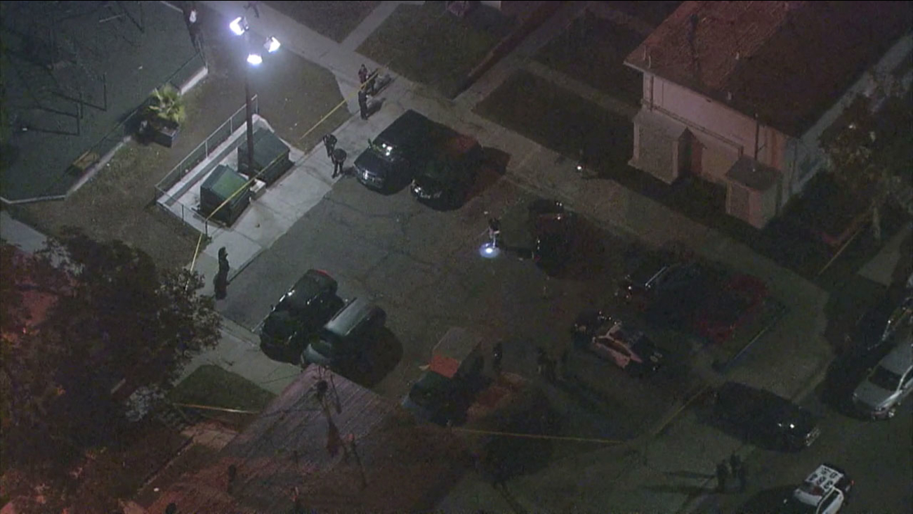 Police investigate the scene in San Pedro where four people were wounded in a shooting.