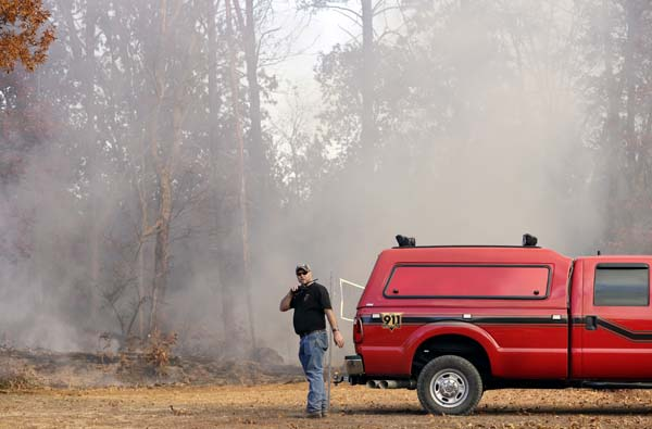 <div class='meta'><div class='origin-logo' data-origin='AP'></div><span class='caption-text' data-credit='AP Photo/Mark Humphrey'>Assistant Chief Dusten Woodard of the Mowbray Volunteer Fire Depart talks on a radio as a crew fights a wildfire Thursday, Nov. 10, 2016, in Soddy-Daisy, Tenn.</span></div>