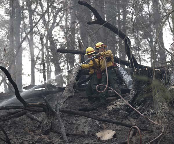 <div class='meta'><div class='origin-logo' data-origin='AP'></div><span class='caption-text' data-credit='AP Photo/John Bazemore'>Firefighters work to cool hot spots after a wildfire burned a hillside in Clayton, Ga.</span></div>