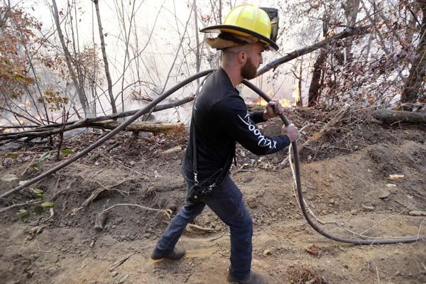 <div class='meta'><div class='origin-logo' data-origin='AP'></div><span class='caption-text' data-credit='AP Photo/Mark Humphrey'>Lieutenant Jesse Mooney, of the Flat Top Mountain Volunteer Fire Department, carries a hose as firefighters battle a wildfire</span></div>