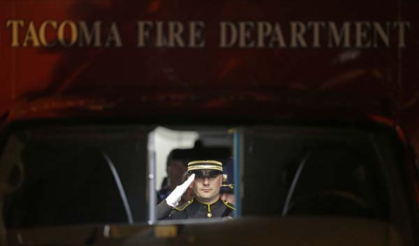 <div class='meta'><div class='origin-logo' data-origin='AP'></div><span class='caption-text' data-credit='AP Photo/Ted S. Warren'>A law enforcement officer salutes as viewed through the windshield of a Tacoma Fire Department as the body is transported</span></div>