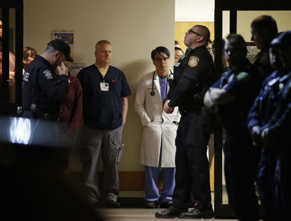 <div class='meta'><div class='origin-logo' data-origin='AP'></div><span class='caption-text' data-credit='AP Photo/Ted S. Warren'>Hospital and law enforcement workers stand at an entrance to Tacoma General Hospital in Tacoma, Wash.</span></div>