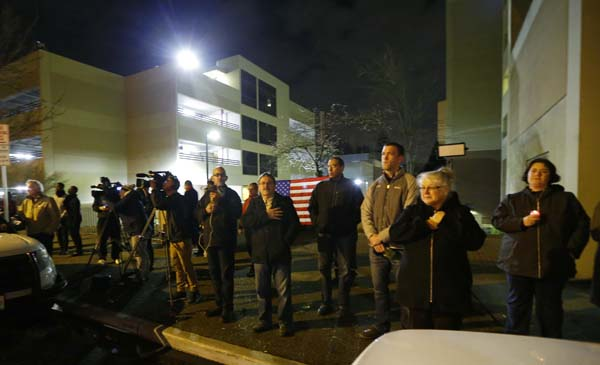 <div class='meta'><div class='origin-logo' data-origin='AP'></div><span class='caption-text' data-credit='AP Photo/Ted S. Warren'>Members of the public holding a candle and a flag join journalists as they wait outside Tacoma General Hospital</span></div>