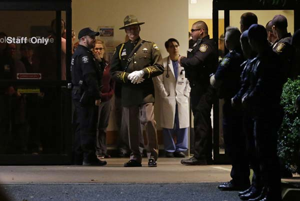 <div class='meta'><div class='origin-logo' data-origin='AP'></div><span class='caption-text' data-credit='AP Photo/Ted S. Warren'>Hospital and law enforcement workers stand at an entrance to Tacoma General Hospital</span></div>