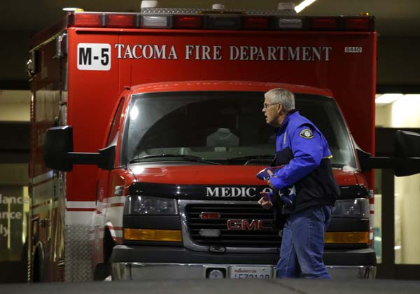 <div class='meta'><div class='origin-logo' data-origin='AP'></div><span class='caption-text' data-credit='AP Photo/Ted S. Warren'>A Lakewood Police chaplain carries a U.S. flag as he walks in front of an ambulance at Tacoma General Hospital</span></div>