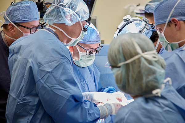"""<div class=""""meta image-caption""""><div class=""""origin-logo origin-image none""""><span>none</span></div><span class=""""caption-text"""">Lead surgeon, Gary Hartman, MD, surrounded by additional members of the team. (David Hodges/Lucile Packard Children's Hospital Stanford)</span></div>"""