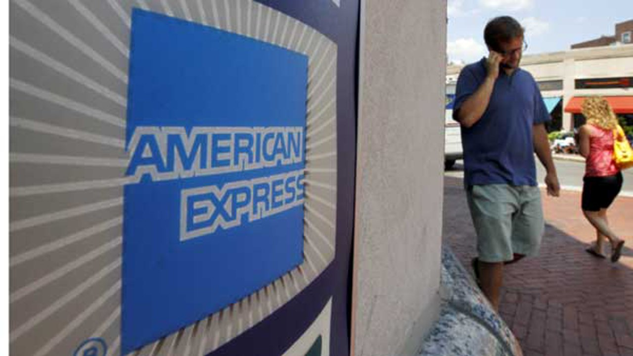 Passers-by walk past an American Express logo near the entrance to a bank in the Harvard Square neighborhood of Cambridge, Mass.