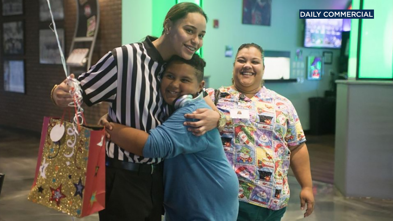 Jadyn Vasquez (left) hugs Jonas Nielsen (center) as his mother Gigi Pena (right) smiles.
