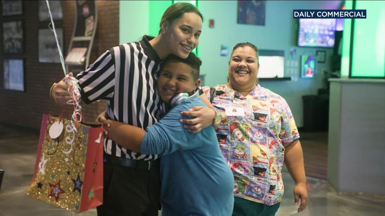 Jadyn Vasquez (left) hugs Jonas Nielsen (center) as his mother Gigi Pena (right) smiles.