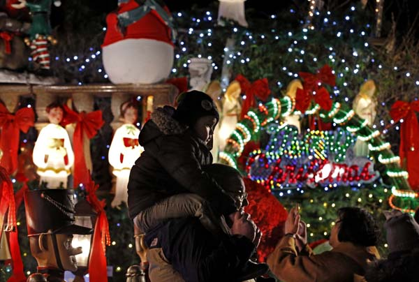<div class='meta'><div class='origin-logo' data-origin='AP'></div><span class='caption-text' data-credit='AP Photo/Kathy Willens)'>A man and his child pass Christmas decorations in the Dyker Heights neighborhood of the Brooklyn borough of New York</span></div>