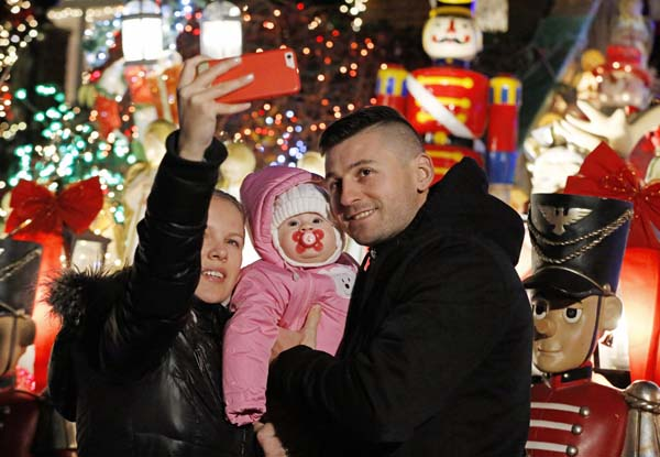 <div class='meta'><div class='origin-logo' data-origin='AP'></div><span class='caption-text' data-credit='AP Photo/Kathy Willens'>Tanya, Adriana and Vasyl Palinchak take a selfie in front of an elaborately-decorated home in the Dyker Heights neighborhood</span></div>
