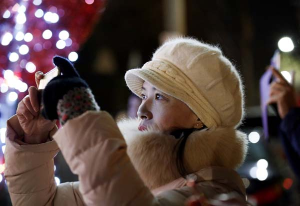 <div class='meta'><div class='origin-logo' data-origin='AP'></div><span class='caption-text' data-credit='AP Photo/Kathy Willens'>Jian Qing Chen, a recent arrival to New York from China's Fujian province, snaps a cell phone photo of Christmas decorations in the Dyker Heights neighborhood</span></div>