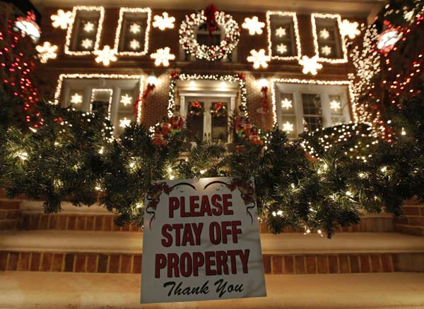 <div class='meta'><div class='origin-logo' data-origin='AP'></div><span class='caption-text' data-credit='AP Photo/Kathy Willens'>A sign in front of a decorated house warns visitors to keep off the premises in the Dyker Heights neighborhood of New York</span></div>