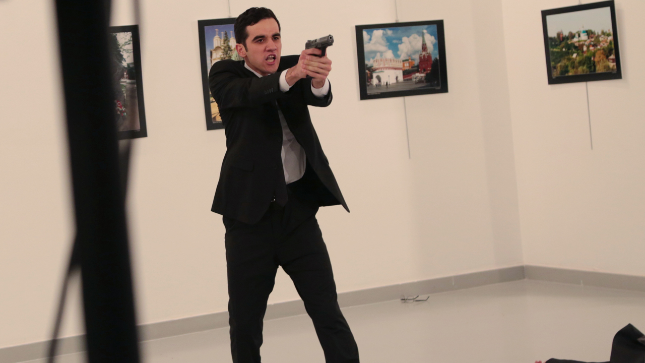 An unnamed gunman gestures after shooting the Russian Ambassador to Turkey, Andrei Karlov, at a photo gallery in Ankara, Turkey, Monday, Dec. 19, 2016.