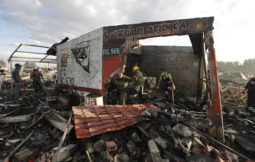 <div class='meta'><div class='origin-logo' data-origin='AP'></div><span class='caption-text' data-credit='AP Photo/Eduardo Verdugo'>Firefighters and rescue workers remove debris from the scorched ground of Mexico's best-known fireworks market after an explosion explosion ripped through it.</span></div>