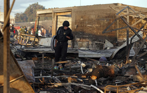 <div class='meta'><div class='origin-logo' data-origin='AP'></div><span class='caption-text' data-credit='AP Photo/Eduardo Verdugo'>A Mexico State policeman looks through the scorched ground of the open-air San Pablito fireworks market, in Tultepec, outskirts of Mexico City.</span></div>