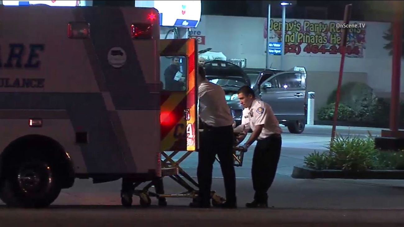 A stabbing victim is placed into an ambulance after a woman stabbed two people in Santa Fe Springs on Tuesday, Dec. 20, 2016.