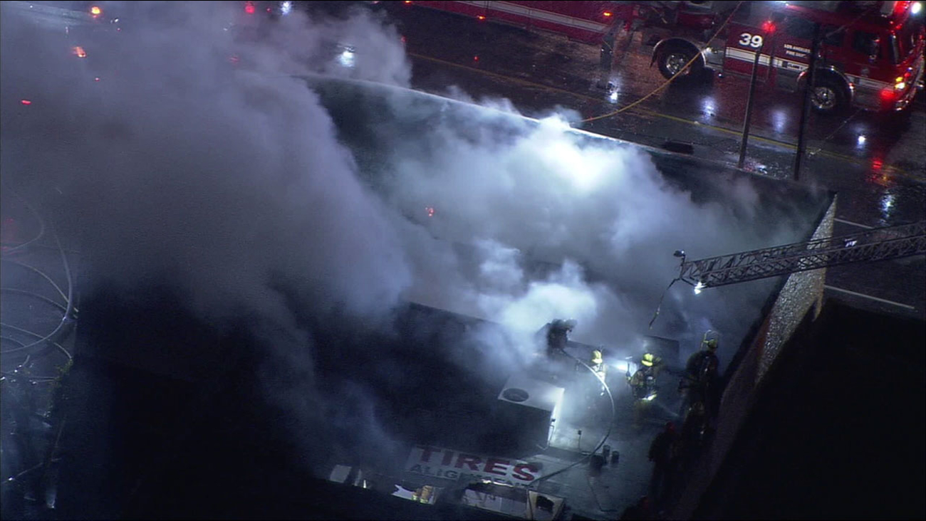 Los Angeles firefighters are seen extinguishing a brief yet explosive fire in a building in Van Nuys on Wednesday, Dec. 21, 2016.