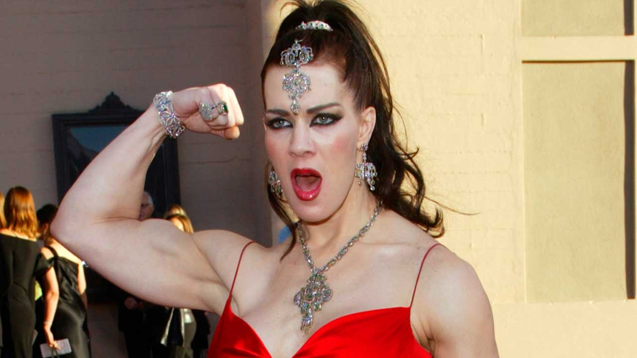 In this Nov. 16, 2003, file photo, Joanie Laurer, former pro wrestler known as Chyna, flexes her bicep as she arrives at the 31st annual American Music Awards, in Los Angeles.