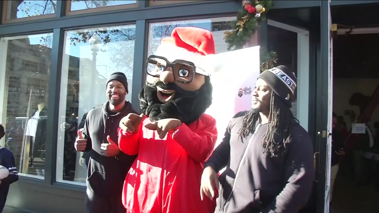 Barron Davis and Marshawn Lynch pose with Black Santa at Lynch's Beast Mode store in Oakland, Calif. on Dec. 22, 2016.